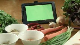 妇女烹调食物并且观看在片剂的食谱 影视素材