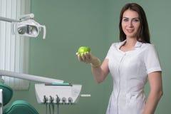 妇女牙医医生在拿着绿色苹果计算机的牙齿办公室 免版税库存图片