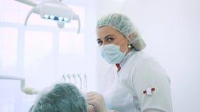 妇女牙医在办公室 一位女性医生牙医在一名男性患者的下颌和牙工作 看照相机 影视素材