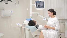 妇女牙医审查并且咨询患者 椅子的年轻非裔美国人的男性患者在牙齿诊所 医学 股票视频