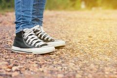 妇女牛仔裤和走在夏季自然的石路的运动鞋鞋子在背景 免版税库存图片