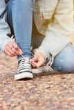 妇女牛仔裤和走在夏季自然的石路的运动鞋鞋子在背景 库存图片