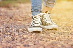 妇女牛仔裤和走在石roadon的运动鞋鞋子在背景的夏季自然 免版税库存照片