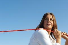 妇女牵索天空背景 免版税库存图片