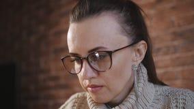 妇女特写镜头戴专心地运作的眼镜的在膝上型计算机上 研究膝上型计算机,妇女特写镜头面孔的工程师  股票录像