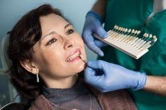 妇女特写镜头画象在牙齿诊所办公室 检查和选择牙的颜色牙医 牙科 免版税库存照片