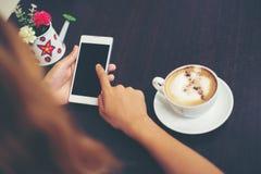 妇女特写镜头递与她的机动性的正文消息在咖啡 免版税图库摄影