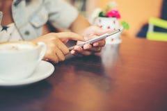 妇女特写镜头递与她的机动性的正文消息在咖啡 库存照片