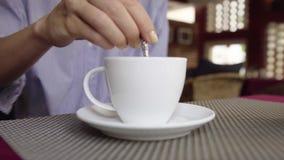 妇女特写镜头搅动热的饮料咖啡或茶在咖啡馆 股票视频