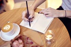 妇女特写镜头递在笔记本,布局的空白页的文字 在木桌上的花在现代咖啡馆 St华伦泰 免版税库存照片