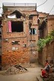 妇女现在坐她的地震被破坏的房子外在Bhaktapu 免版税图库摄影
