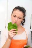 妇女用一把菠菜在一个现代厨房里 免版税库存图片