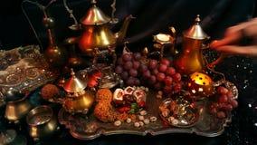 妇女用东方jewelery饮用的茶和吃传统摩洛哥甜点 杯番红花Masala牛奶茶 股票录像