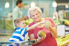 妇女用儿童购物果子 免版税库存照片