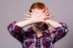 妇女用发信号她的手停止在一灰色backgr隔绝了 免版税库存图片
