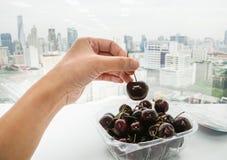 妇女用吃的新鲜的樱桃 库存照片