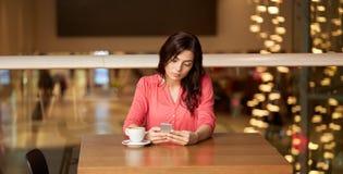 妇女用咖啡和智能手机在餐馆 免版税图库摄影