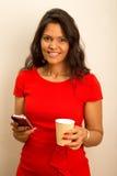 妇女用咖啡和电话 库存图片