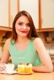 妇女用咖啡和蛋糕在厨房里 暴食 库存照片