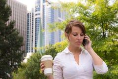妇女用咖啡在使用巧妙的电话的都市公园 库存图片