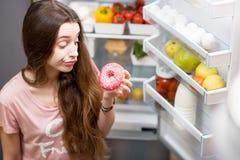 妇女用在冰箱附近的甜食物 图库摄影