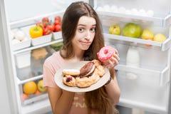 妇女用在冰箱附近的甜食物 免版税库存照片