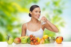 妇女用在桌饮用水的健康食物 图库摄影