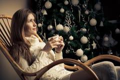 妇女用在椅子的咖啡。 圣诞节decorati 免版税库存照片