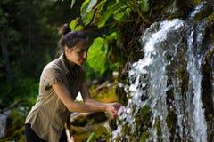 妇女用在瀑布的两只手 库存照片