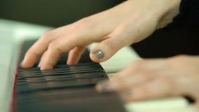 妇女用在白色数字式钢琴,与defocus的特写镜头射击的人工使用 女孩由在键盘的手指使用或 影视素材