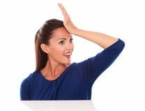 妇女用在看起来的前额的手惊奇 免版税库存照片
