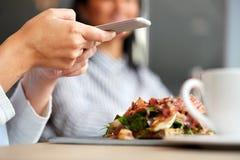 妇女用在餐馆的智能手机和火腿沙拉 免版税图库摄影