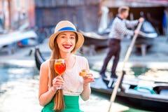 妇女用在水chanal附近的意大利开胃酒在威尼斯 免版税库存照片