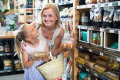 妇女用女儿买的曲奇饼在商店 库存图片