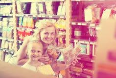 妇女用女儿买的曲奇饼在商店 免版税库存照片