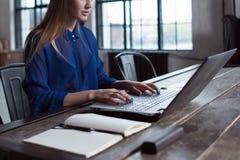 妇女用她的在膝上型计算机键盘的手 设计师在有笔记本和计算机的工作台坐它 免版税库存照片