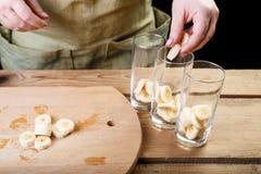 妇女用她的手放香蕉片断入三块空的玻璃玻璃 库存照片