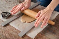 妇女用她的手滚动一个曲奇饼的酥皮点心与滚动的pi 库存图片