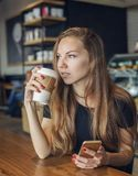 妇女用手机饮用的咖啡和认为 库存图片