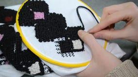 妇女用手绣在白色织品的乌克兰刺绣与在留下的箍的黑羊毛螺纹看法特写镜头 股票录像
