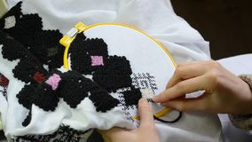 妇女用手绣在白色织品的乌克兰刺绣与在箍的黑羊毛螺纹看法 影视素材