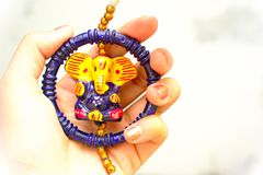 妇女用拿着印度神阁下ganesha的美好的五颜六色的神象俏丽的手通常被卖在ganesha chaturthi和diwa期间 免版税库存照片