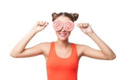 妇女用拿着在眼睛的小圆面包棒棒糖 库存照片