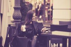 妇女用智能手机饮用的咖啡 库存图片