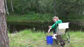 妇女用桶提的抓住鱼用水 活跃猫宠物抓住鱼 免版税库存图片