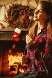 妇女用由壁炉的蛋白软糖 微笑的少妇和 库存图片