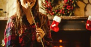 妇女用由壁炉的蛋白软糖 微笑的少妇和 免版税库存图片