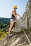 妇女用站立在岩石的上升的设备 免版税库存图片