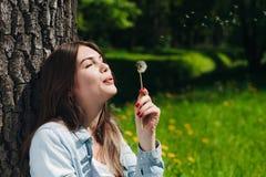 妇女用蒲公英在公园 免版税库存照片