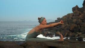 妇女用被举的手弯曲身体在海洋慢动作 股票录像